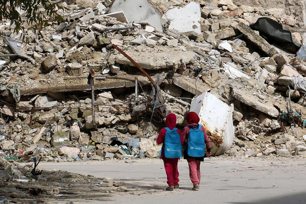 Students walk past rubble pile on their walk to school  -Google Images