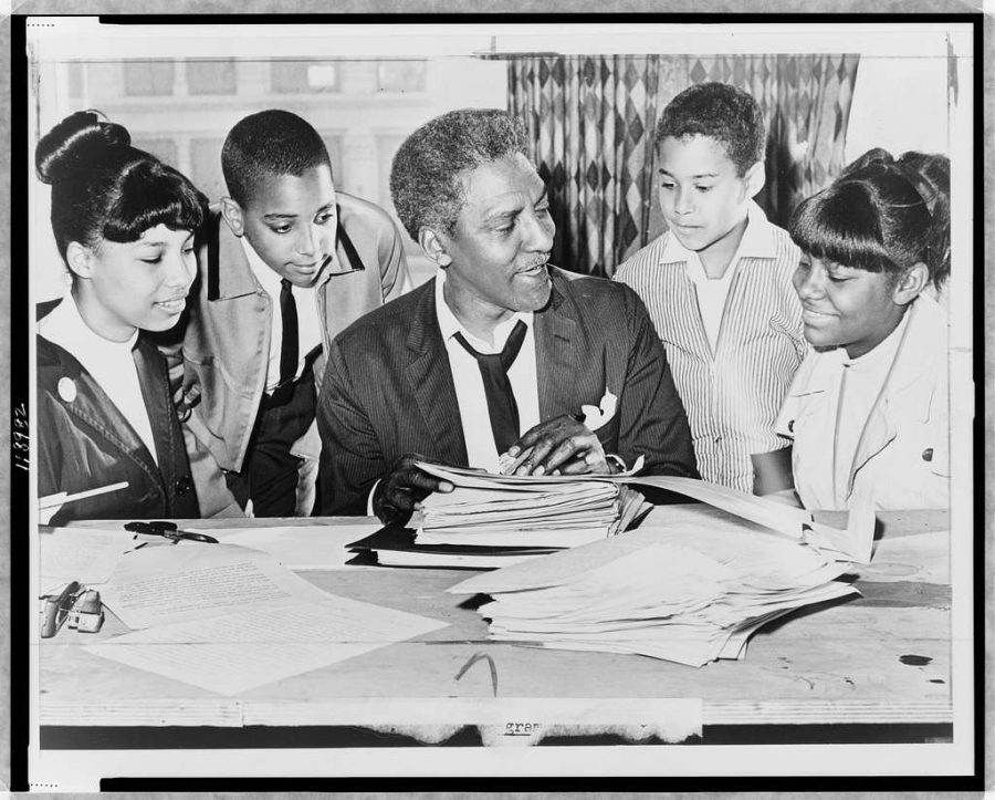 Bayard Rustin (center) speaking with (left to right) Carolyn Carter, Cecil Carter, Kurt Levister, and Kathy Ross, before demonstration