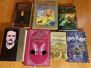 Top Right to Bottom Left: The Picture of Dorian Gray; The Wizard of Oz; The Lightning Thief; The Collected Tales and Poems of Edgar Allan Poe; Alice in Wonderland; The Fellowship of the Ring; The Sorcerer